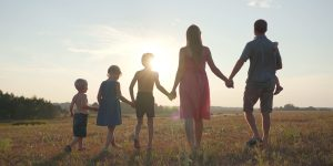 Family walking across field holding hands